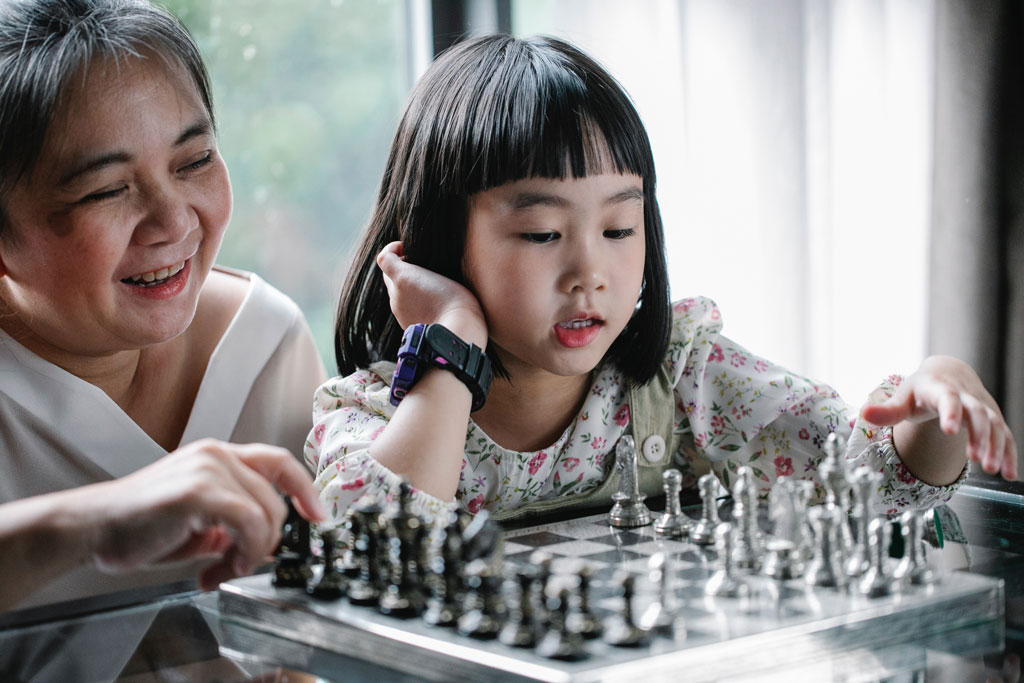 Older woman teaching her granddaughter chess